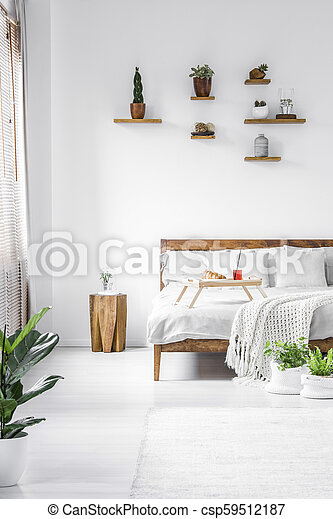 Rustic White Bedroom Interior Wooden Stool Next To Bed In Rustic White Bedroom Interior With Plants On Shelves Canstock