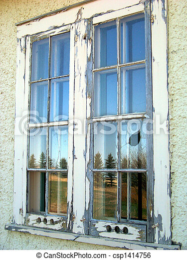 Rustic windowpanes in an abandoned building reflect the country side. - csp1414756