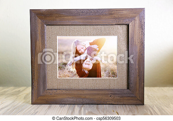 Rustic Wood Framed Portrait of a Mother and Her Baby Playing Outside at Sunset - csp56309503