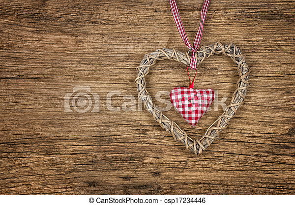 Rustic wooden background with a braided heart - csp17234446