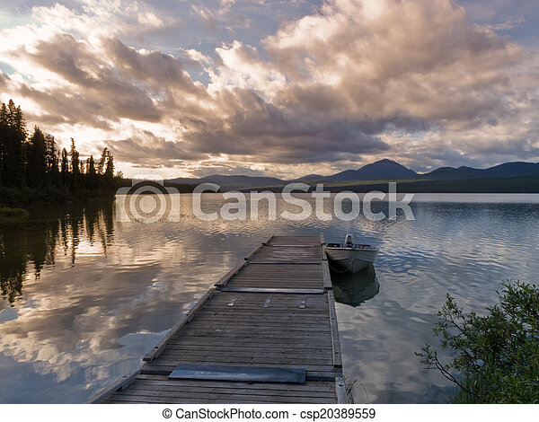 Rustic wooden float dock jetty boat tranquil lake - csp20389559