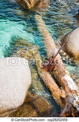 Rusty anchor at the rocks - csp28252459