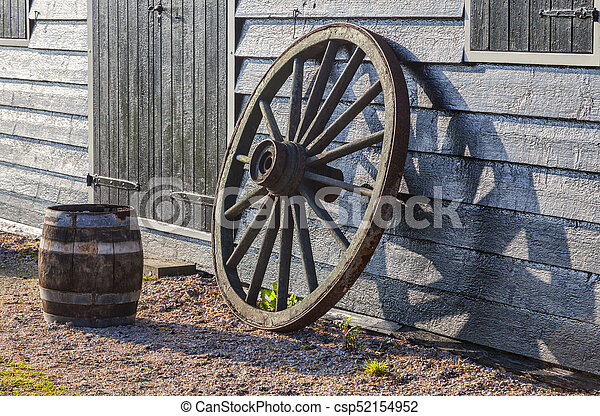 Image of a rusty old wheel and a barrel near a the wall of a rusty old wheel csp52154952 publicscrutiny Choice Image