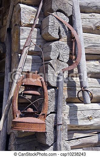 rusty sickle and kerosene lamp on old farm wall - csp10238243