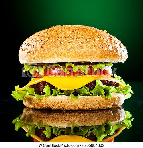 Una hamburguesa deliciosa y apetitosa en un verde oscuro - csp5884802
