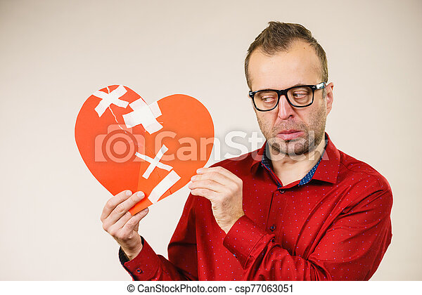 Sad adult man holding broken heart - csp77063051