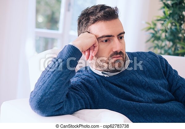 Sad and depressed portrait of man alone at home - csp62783738