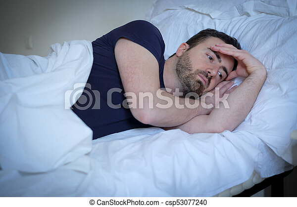 Sad and upset man trying to sleep in bed - csp53077240