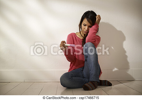 Sad Asian woman looking at pregnancy test sitting on floor - csp17466715
