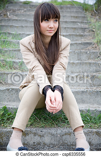 Sad Asian woman sitting on the stairs - csp6335556
