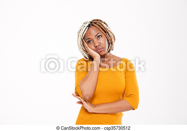 Sad bored african american young woman in yellow dress standing - csp35730512