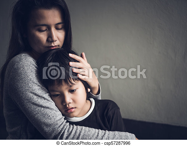 Sad little boy being hugged by his mother at home. Parenthood, Love and togetherness concept. - csp57287996