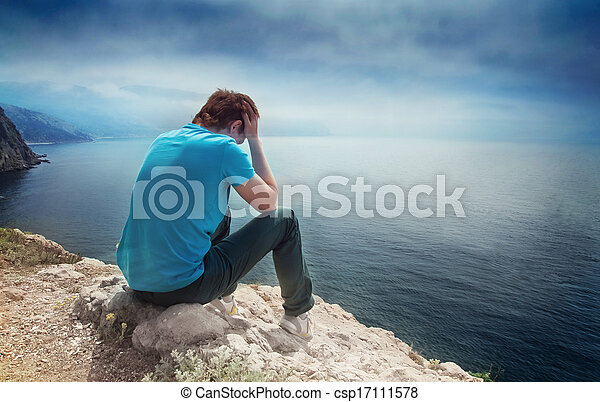 Sad lonely boy on a hill overlooking the sea - csp17111578