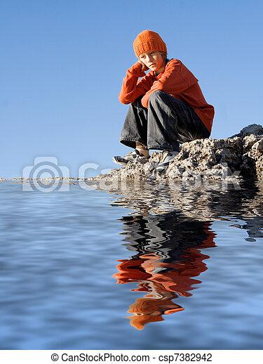 sad lonely depressed child sitting alone outdoors - csp7382942