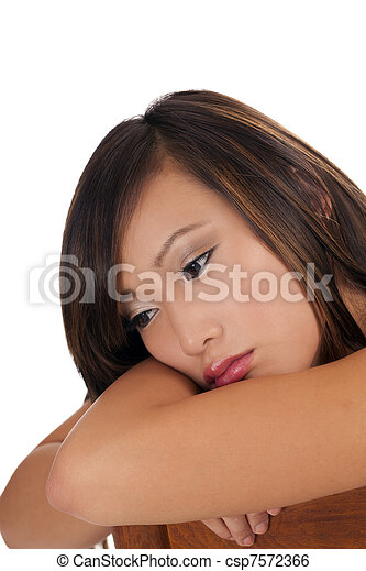 Sad looking Asian person woman head on arms - csp7572366