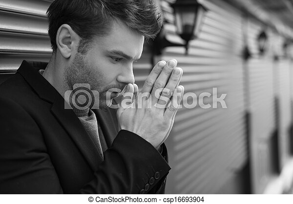 Sad men. Black and white side view of depressed young men holding his hands clasped and looking down while standing outdoors - csp16693904