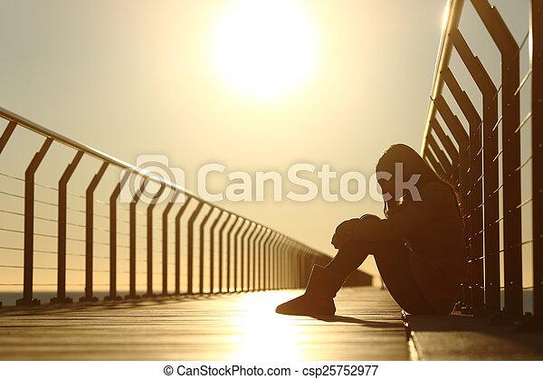Sad teenager girl depressed sitting in a bridge at sunset - csp25752977