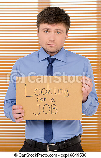 Sad unemployed man is looking for a job. Showing plate with sign  - csp16649530