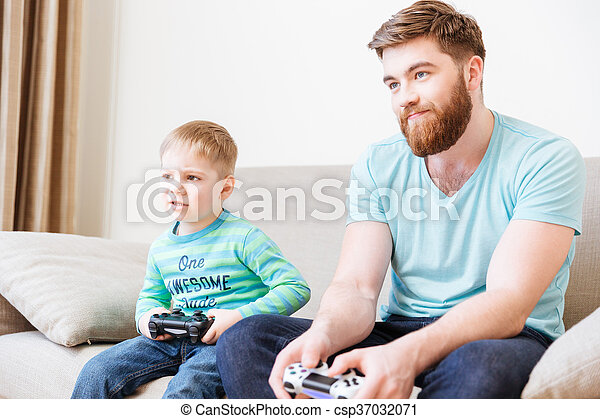 Sad unhappy dad and son playing computer games - csp37032071