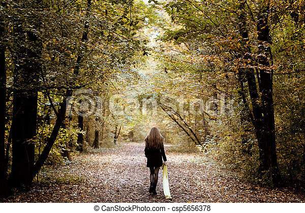 Sad woman walking alone in the woods - csp5656378
