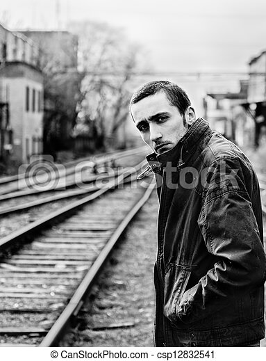 Sad Young Man Waiting For The Train Among Industrial Ruins