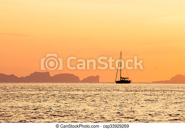 Sailboat on the ocean at sunset - csp33929269