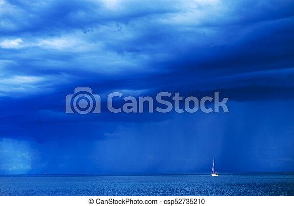 Sailing boat at stormy sea horizon - csp52735210