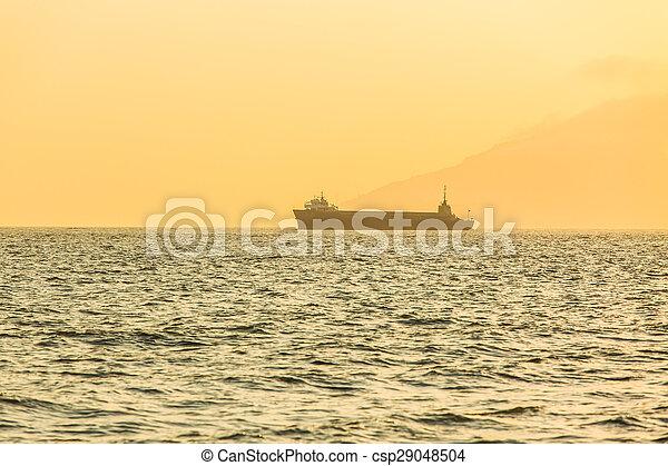 Sailing boat at sunset in ocean - csp29048504