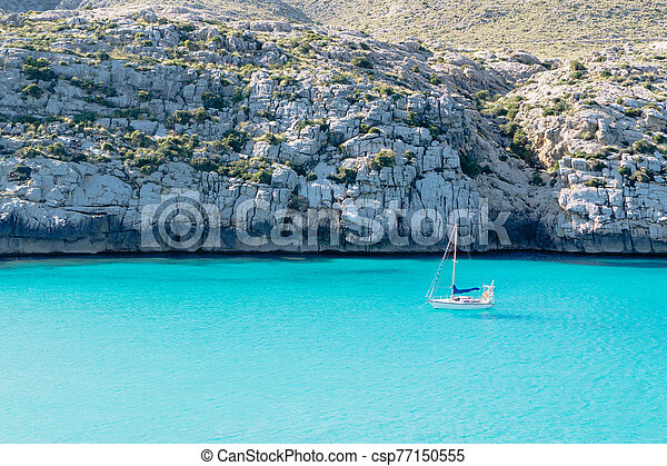 Sailing boat on blue water beach mountain background - csp77150555