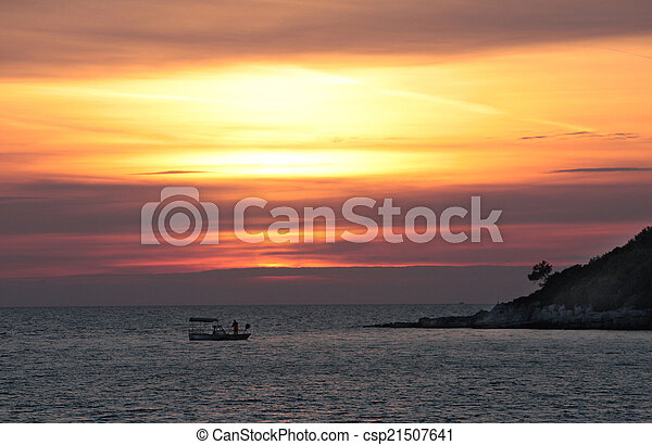 Sailing boats on a background of a beautiful red sunset - csp21507641