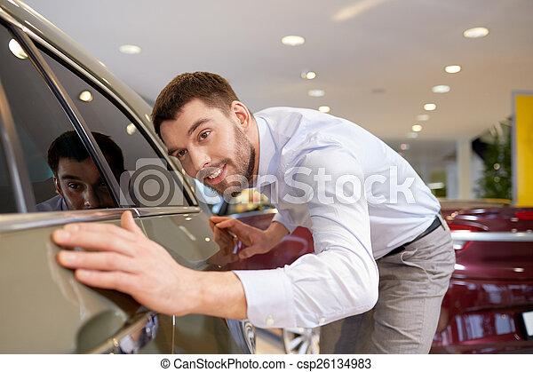 Un hombre feliz tocando el auto en un show o en un salón - csp26134983