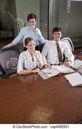 Tres empleados de oficinas trabajando en la sala de juntas - csp4492931
