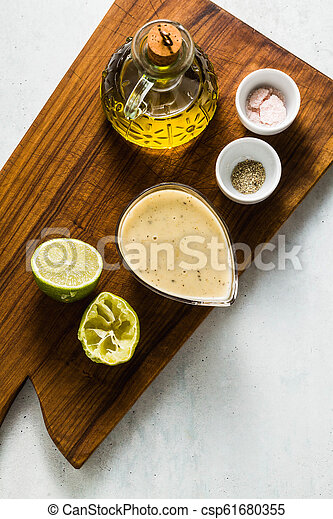 salad dressing of olive oil and lemon juice or lime with seasonings on a cutting wooden board. classic vinaigrette - csp61680355