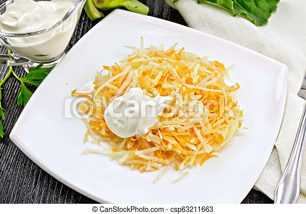 Salad of carrot and kohlrabi with sour cream on black board - csp63211663