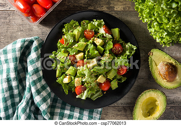 Salad with avocado, lettuce, tomato and flax seeds on wooden table. Top view. - csp77062013