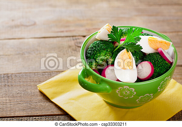Salad with broccoli, eggs and radishes in a small bowl on wooden background with copy space. - csp33303211