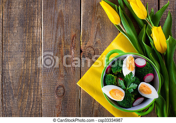 Salad with broccoli, eggs and radishes in a small bowl on wooden background and tulip bouquet, with copy space. - csp33334987