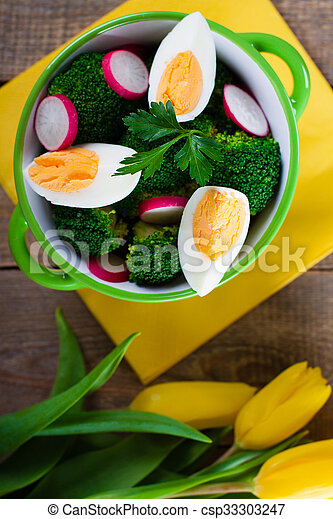Salad with broccoli, eggs and radishes in a small bowl on wooden background and tulip bouquet. - csp33303247