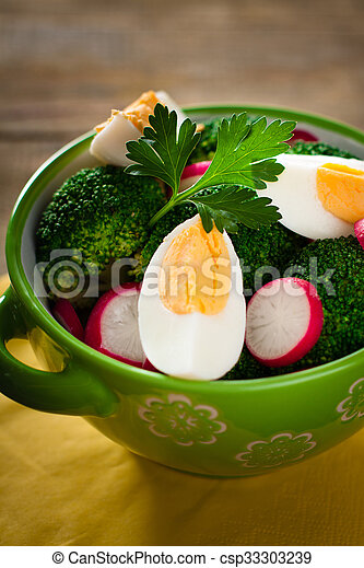 Salad with broccoli, eggs and radishes in a small bowl on wooden background. - csp33303239