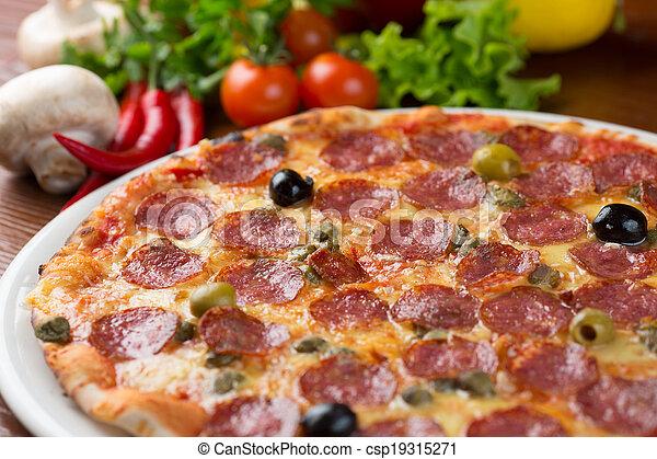 Pizza de salami italiana en la mesa con verduras - csp19315271