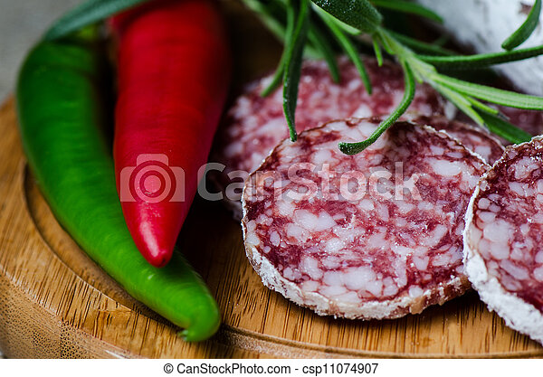 Salami with red and green pepper on wooden cutting board - csp11074907