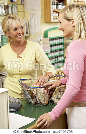 Sales assistant with customer in health food store - csp7491708