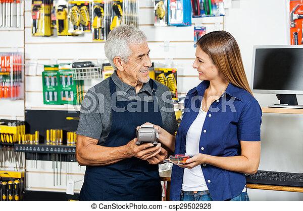 Salesman Holding Electronic Reader While Customer Paying Through - csp29502928