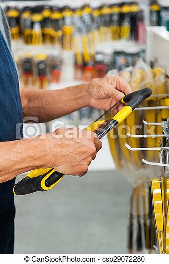 Salesman Holding Hacksaw In Store - csp29072280