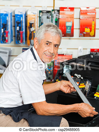 Salesman Holding Tool In Hardware Store - csp29488905