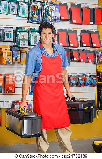 Salesman Holding Toolboxes In Hardware Shop - csp24782189