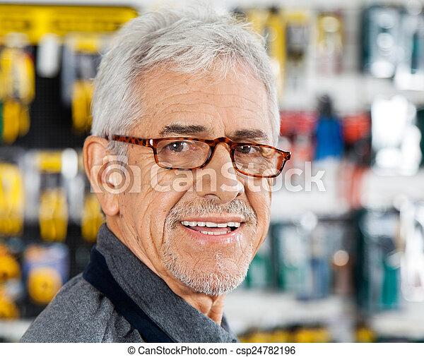 Salesman Smiling In Hardware Store - csp24782196