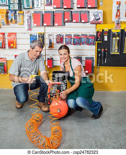 Saleswoman Assisting Customer In Using Air Compressor - csp24782323