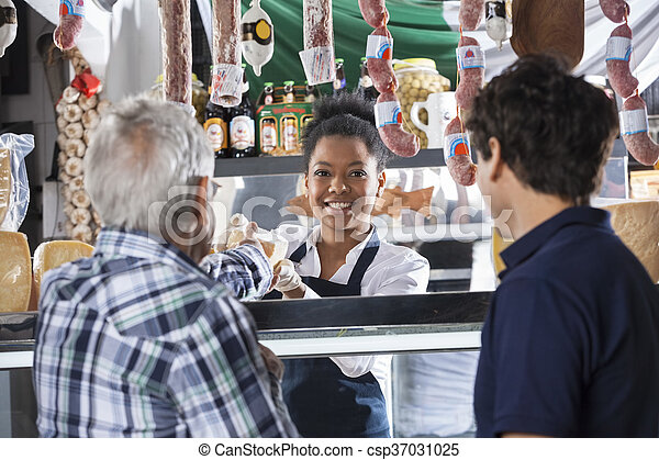 Saleswoman Selling Cheese To Male Customers At Shop - csp37031025