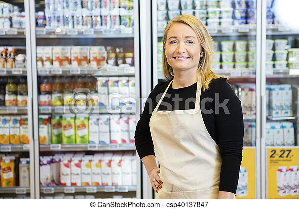 Saleswoman With Hand On Hip Against Refrigerator - csp40137847